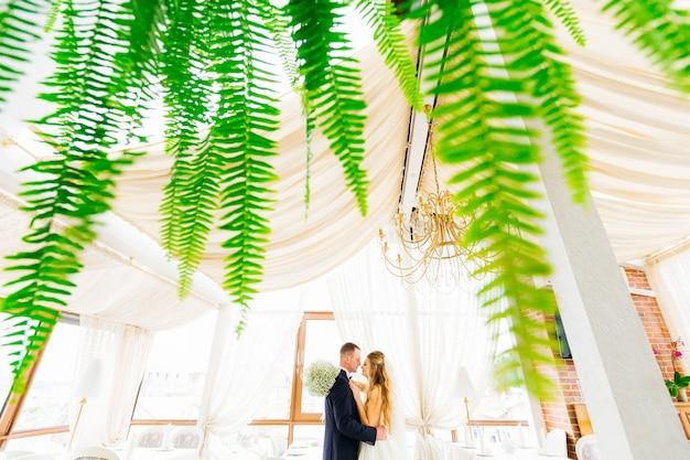 A samambaia sai em primeiro plano, o perfil dos recém-casados nos braços um do outro no corredor do restaurante