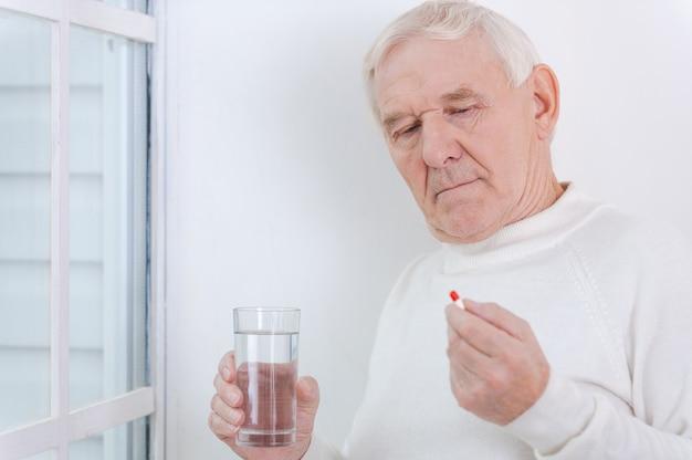 A saúde é o mais importante. homem sênior pensativo segurando medicamentos em pé perto da janela