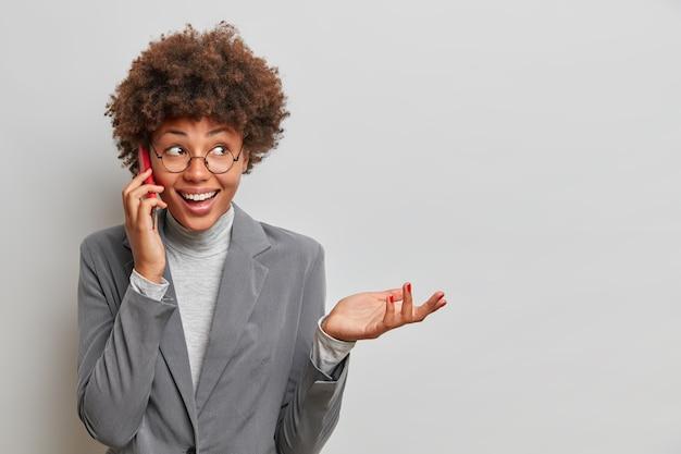 A secretária afro-americana feliz discute questões de trabalho com colega de trabalho via smartphone, recebe ligação do gerente, levanta a mão e ri alegremente, informa sobre estágio de trabalho