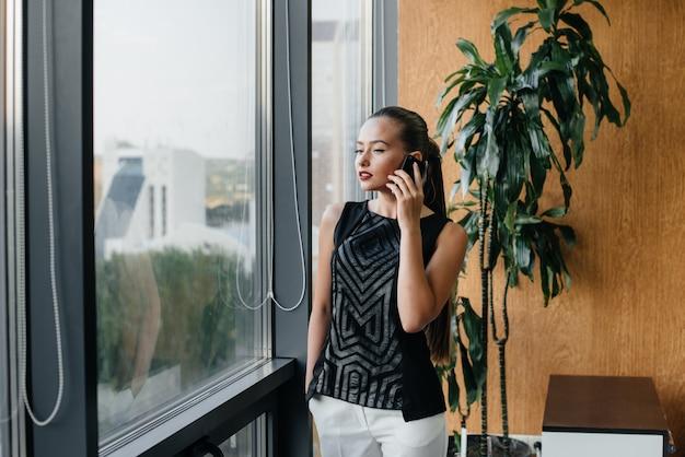A secretária está falando ao telefone perto da janela do escritório