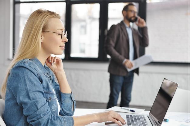 A secretária loira confiante usa o laptop enquanto o chefe conversa ao telefone