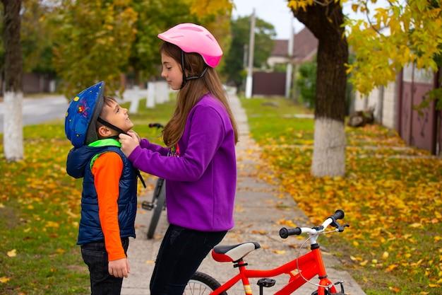 A segurança está em primeiro lugar. a irmã ajuda o irmão mais novo a colocar e prender o capacete protetor. o conceito de segurança, descanso e tempo de permanência. foto com espaço vazio.