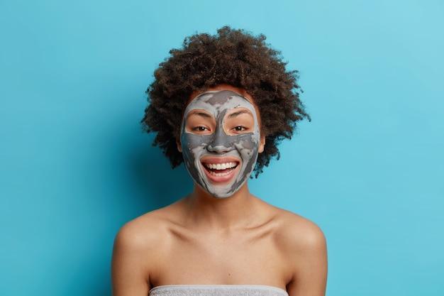 A senhora afro-americana alegre sorri amplamente, tem dentes brancos perfeitos, aplica máscara de argila para remover poros, desfruta de tratamentos de pele, tem o corpo bem cuidado, ombros nus isolados sobre a parede azul