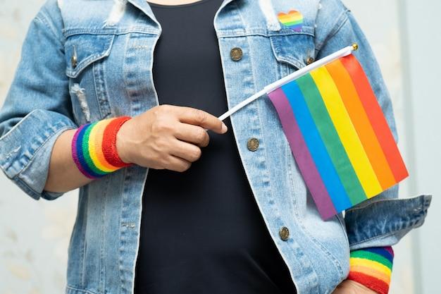 A senhora asiática que guarda a bandeira da cor do arco-íris, símbolo do mês do orgulho de lgbt comemora anual em junho.
