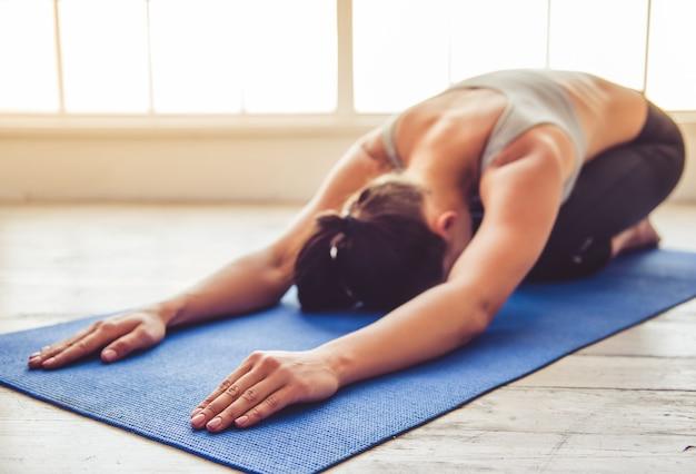 A senhora bonita dos esportes dos jovens está fazendo a ioga no salão da aptidão.