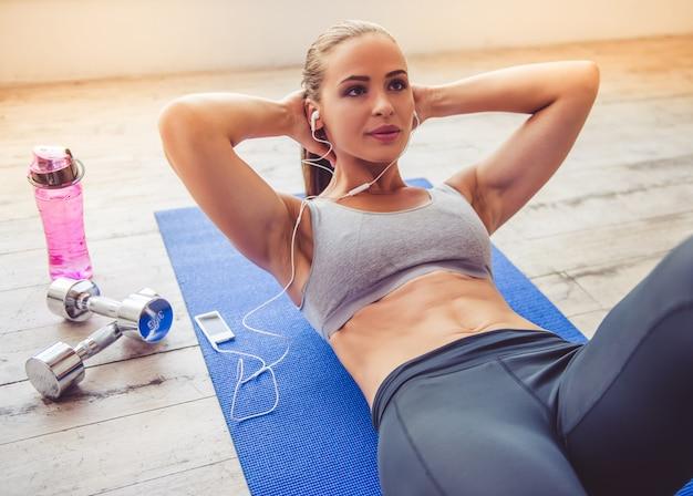 A senhora bonita dos esportes nos fones de ouvido está escutando a música.