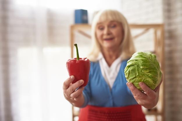 A senhora caseiro dos ingredientes da salada oferece vegetais.
