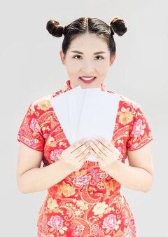A senhora chinesa com cheongsam tem um envelope