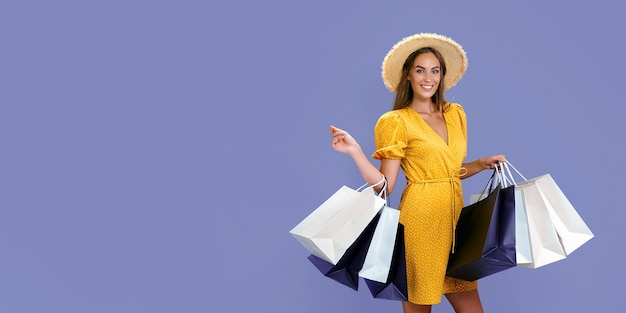 A senhora com aparência bonita carrega roupas novas enquanto segura pacotes coloridos com fundo colorido, grandes vendas