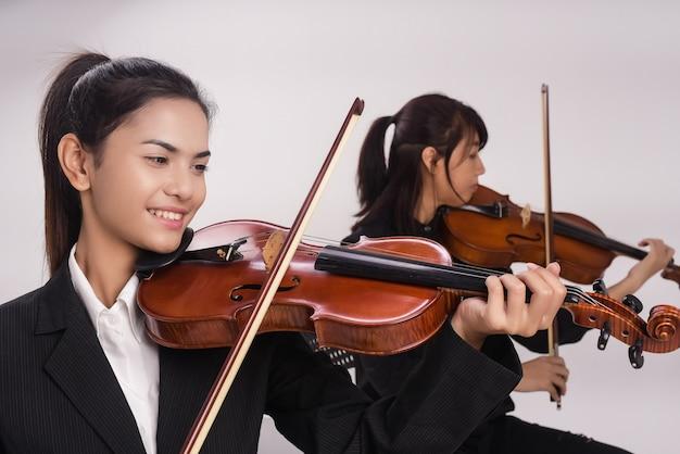 A senhora com violino está tocando música na frente da senhora está jogando viola