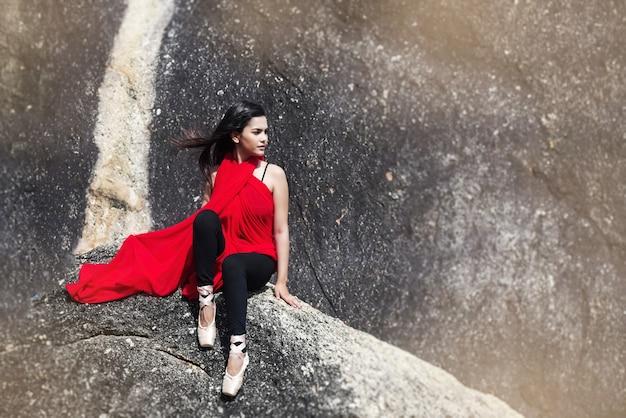 A senhora da beleza usando vestido vermelho e sapatos de balé de cetim