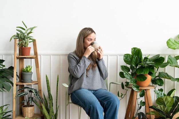 A senhora da planta descansando e tomando um gole no canto da planta