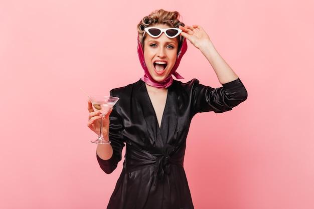 A senhora de vestido preto tira os óculos e posa alegremente com um martini