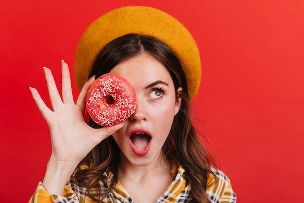 A senhora ergue os olhos com surpresa, cobrindo os olhos com um donut apetitoso. menina com chapéu laranja de espanto, posando na parede vermelha.