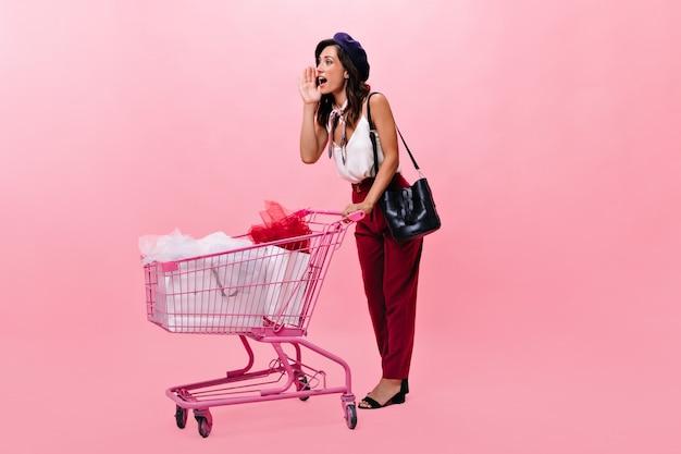 A senhora está gritando e carregando um carrinho de compras rosa. retrato de mulher em calças vermelhas e com lenço em volta do pescoço e com bolsa preta em fundo isolado.