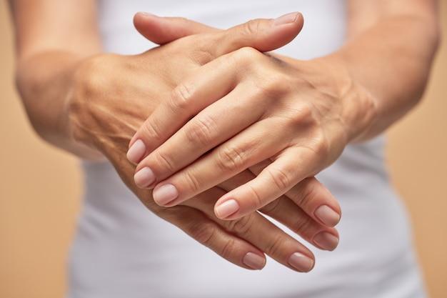 A senhora está usando um hidratante cosmético para as mãos