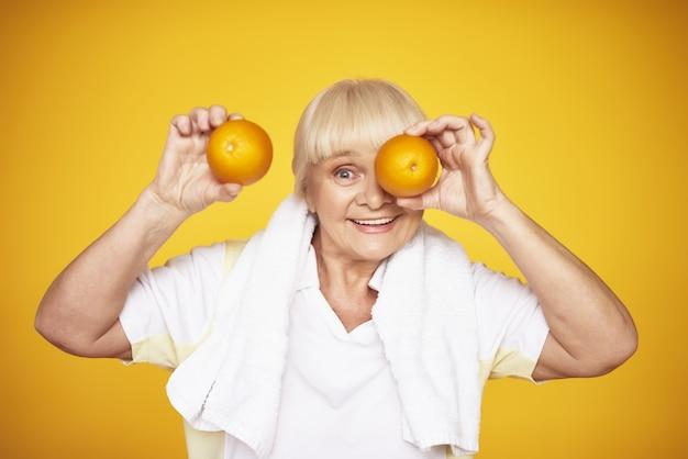 A senhora idosa brincalhão prende o conceito da vitamina c das laranjas.