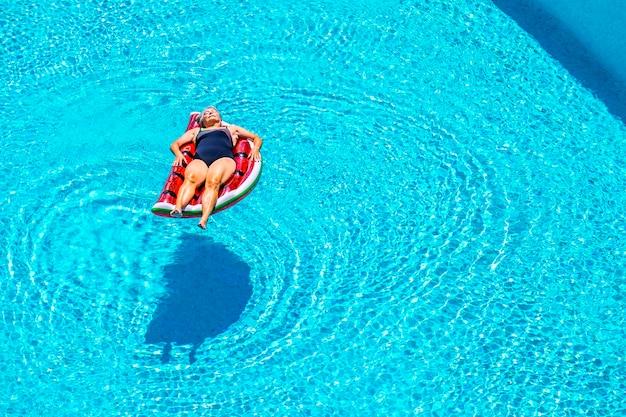 A senhora idosa dorme e relaxa apreciando a água azul da piscina deitada na melancia vermelha lilo