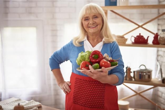 A senhora idosa orgulhosa feliz na cozinha prende vegetais.
