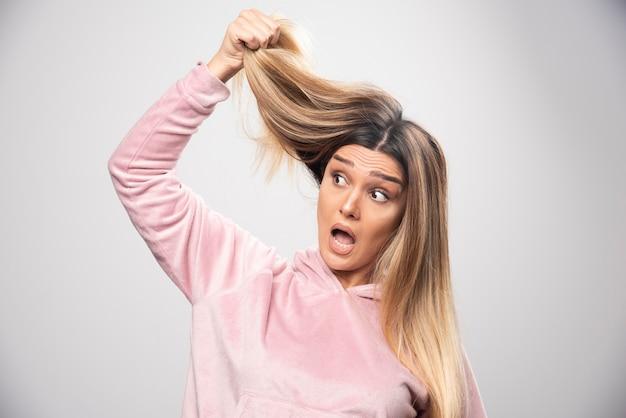 A senhora loira com um moletom rosa se sente insatisfeita com seu cabelo seco ou cor de cabelo.