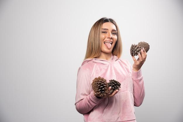 A senhora loira em um moletom rosa faz caretas positivas bobas com cones de carvalho na mão.