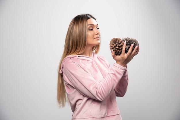 A senhora loira em um moletom rosa faz uma cara positiva e feliz segurando cones de carvalho.