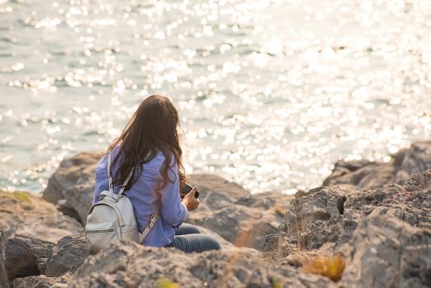 A senhora longa do cabelo senta-se no porco pelo mar antes do telefone móvel esperto da posse da mão do por do sol.
