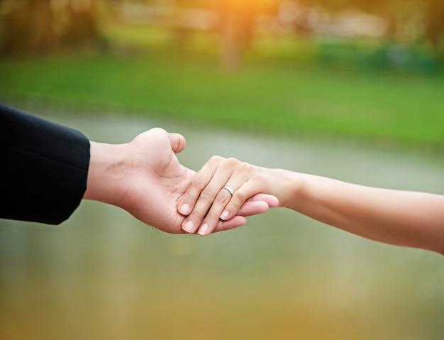 A senhora mão toque na mão do marido, sinal de amor, por confiança e cuidado
