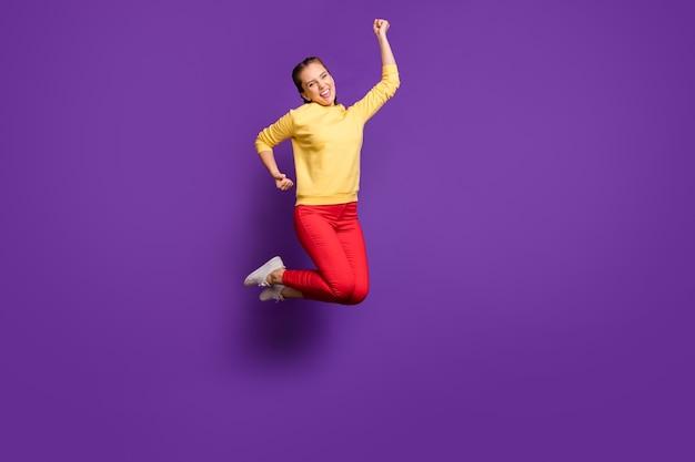 A senhora milenar louca de corpo inteiro pulando alto celebrando a competição do campeão usar calças casuais amarelas pulôver vermelho isolado na parede roxa