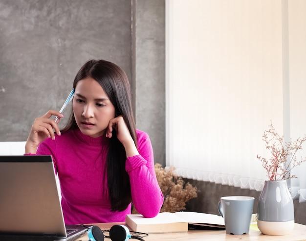 A senhora que trabalha em casa, verificando a ordem do laptop, trabalhando em casa