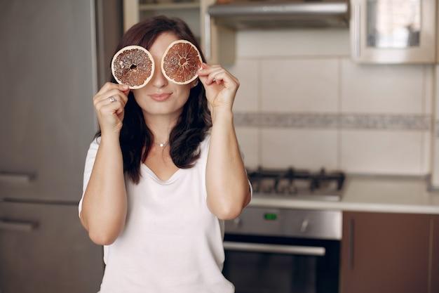 A senhora sorri para a câmera. confeiteiro cozinha na cozinha. cook está descansando.