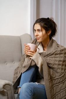 A senhora sorridente em roupas da moda inteligente está sentada na poltrona com uma xícara de chá.