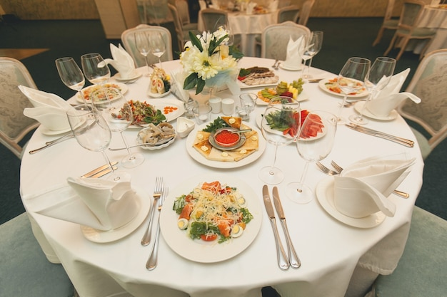 A servir uma mesa festiva com pratos variados. saladas, peixes, frutas, legumes, copos, talheres em uma mesa brilhante.