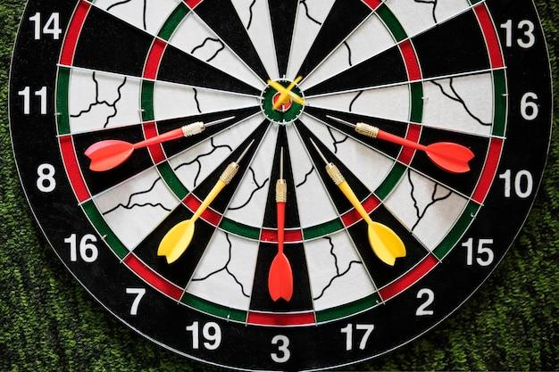 A seta amarela do dardo vencedor atingiu o alvo central do alvo de dardos e outro conceito de competição de marketing de metáfora de perdedor de seta, sobre fundo verde escuro. jogando dardos