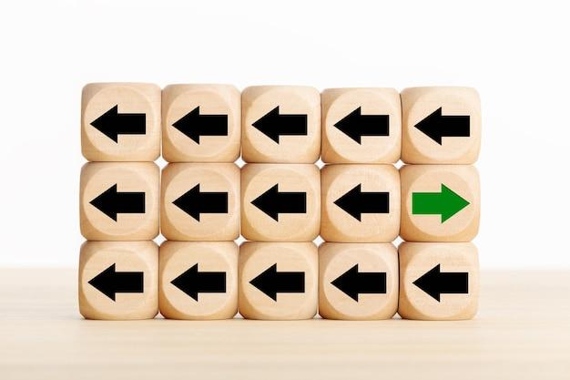 A seta verde apontando para o lado oposto disruptivo das setas pretas em blocos de madeira. pense em um conceito diferente, único ou independente