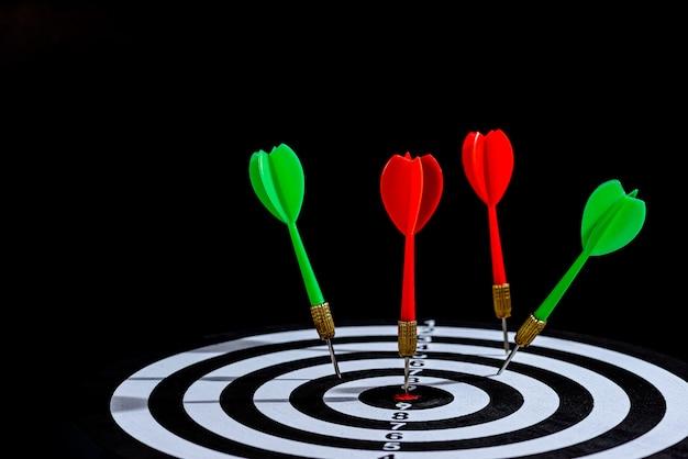 A seta vermelha e verde do dardo que bate no centro do alvo é placa de dardo isolada