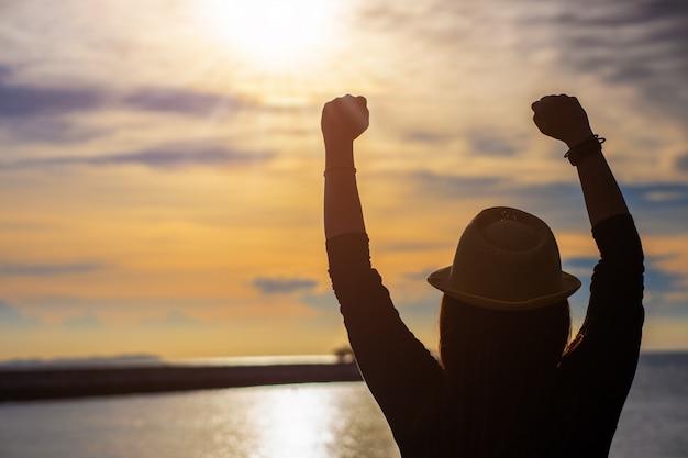 A silhueta da jovem mulher que aprecia a vitória e levanta a mão e grita, aprecia o sucesso.