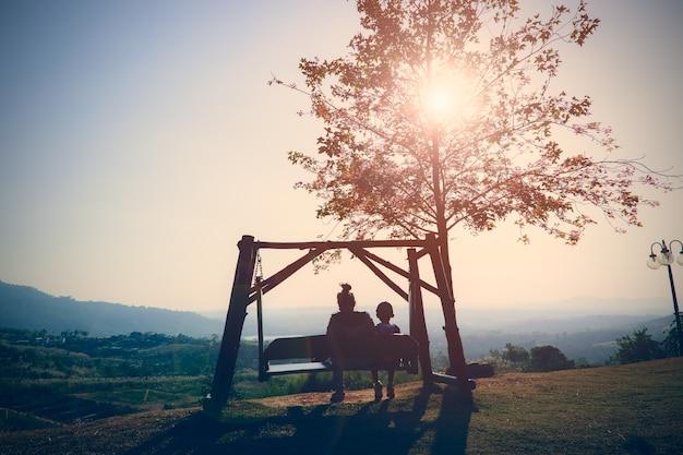 A silhueta da mãe e do filho senta-se em um balanço de madeira na montanha com por do sol bonito.