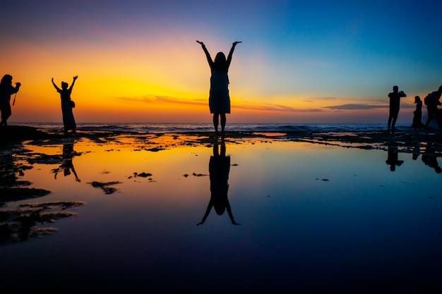 A silhueta da mulher mostra a mão acima e sente feliz na praia com céu colorido.
