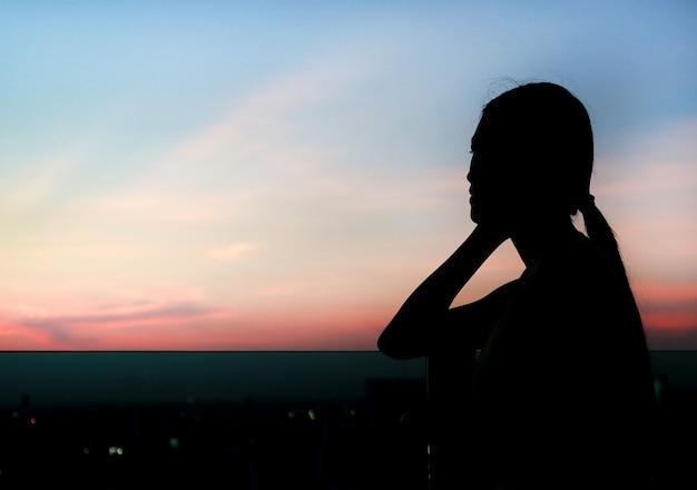 A silhueta da mulher relaxa no por do sol no telhado do edifício.