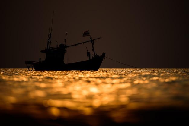 A silhueta de barco de pescador no mar com o céu do sol