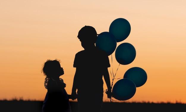 A silhueta de dois filhos, irmão e irmã, pôr do sol