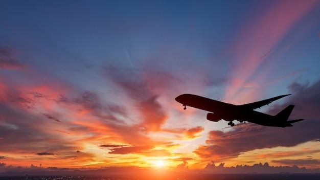 A silhueta de um avião de passageiros que voa no pôr do sol.