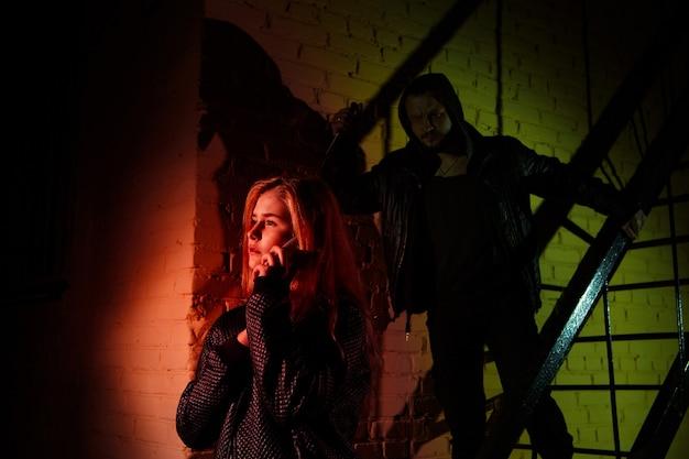 A silhueta de um homem carrega uma faca e segue uma jovem em um túnel escuro. violência contra o conceito de mulheres. pessoas reais, copie o espaço