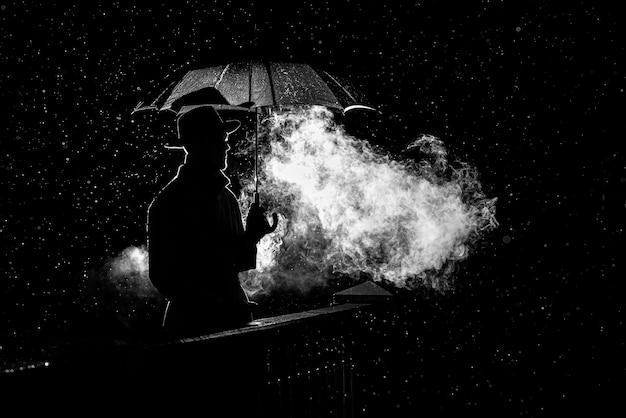 A silhueta de um homem com um chapéu sob um guarda-chuva à noite na chuva na cidade no antigo estilo noir do crime