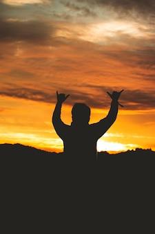 A silhueta de um homem fazendo um sinal com os dedos no céu colorido do pôr do sol