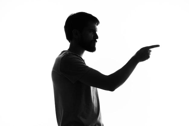A silhueta de um homem gesticula com as mãos em preto e branco.