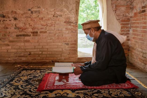 A silhueta de um homem muçulmano lendo o gur'an na velha mesquita, ayutthaya, tailândia