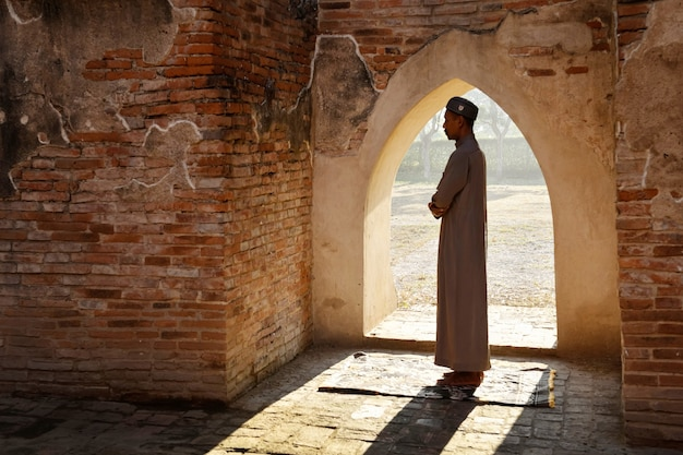 A silhueta de um homem muçulmano orando em uma antiga mesquita na província de phra nakhon si ayutthaya, na ásia.