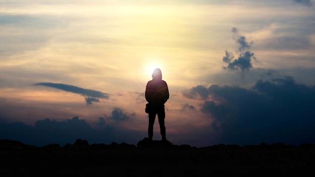 A silhueta de um homem segurando uma câmera e observando o pôr do sol